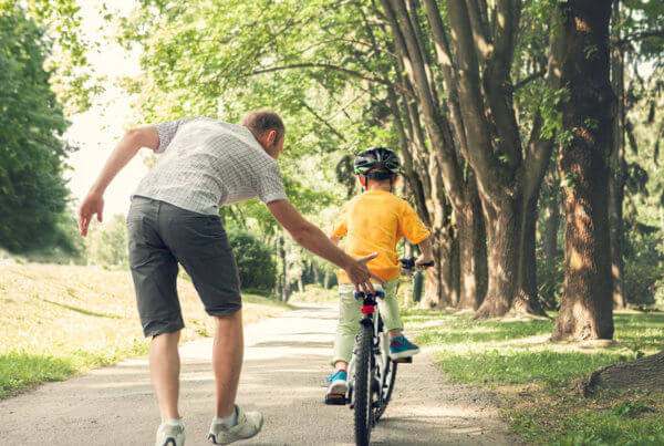 Man-Pushing-Son-on-Bike